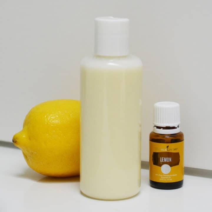 bottle of clarifying shampoo with whole lemon and bottle of lemon essential oil