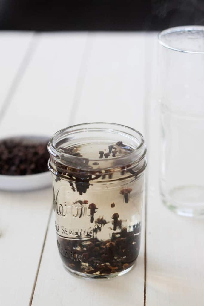 mason jar of whole cloves steeping in water