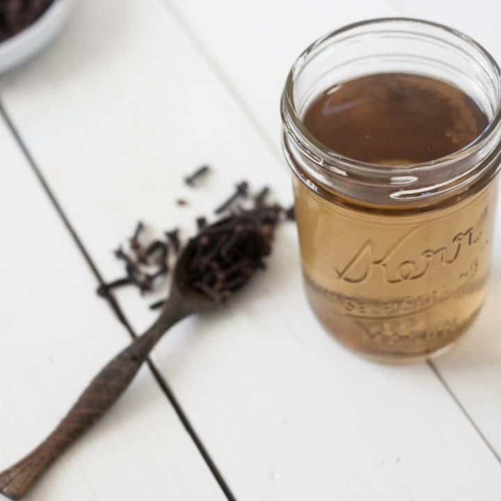 jar of clove mouthwash with wooden teaspoon of whole cloves