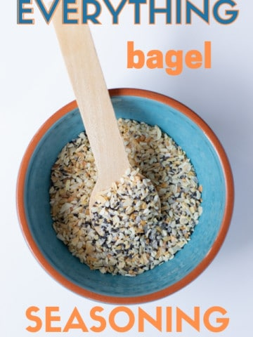 everything bagel seasoning in a teal bowl with a wooden spoon sitting on a white background