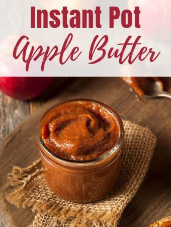 cutting board with burlap napkin with jar of apple butter and spoon