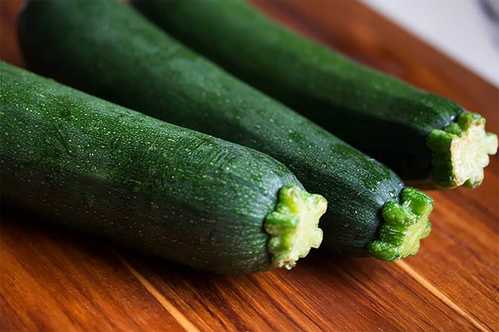 whole zucchini on wooden cutting board