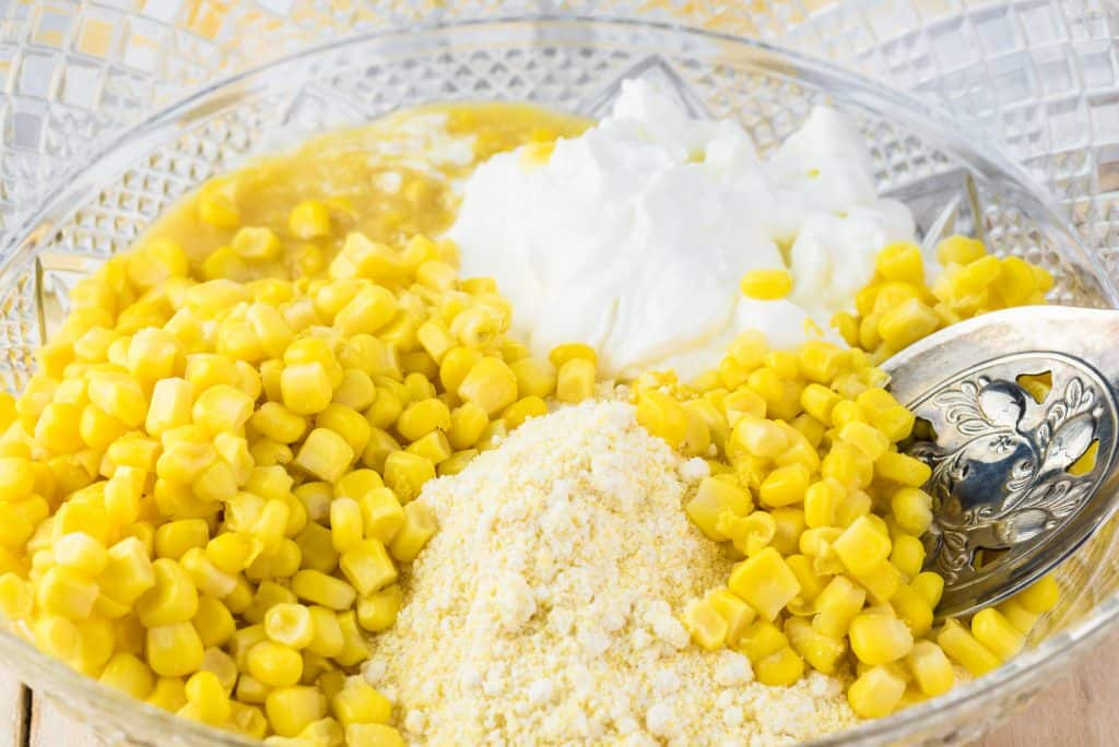 whole corn, creamed corn, corn muffin mix, sour cream, eggs and melted butter in a glass bowl with a spoon