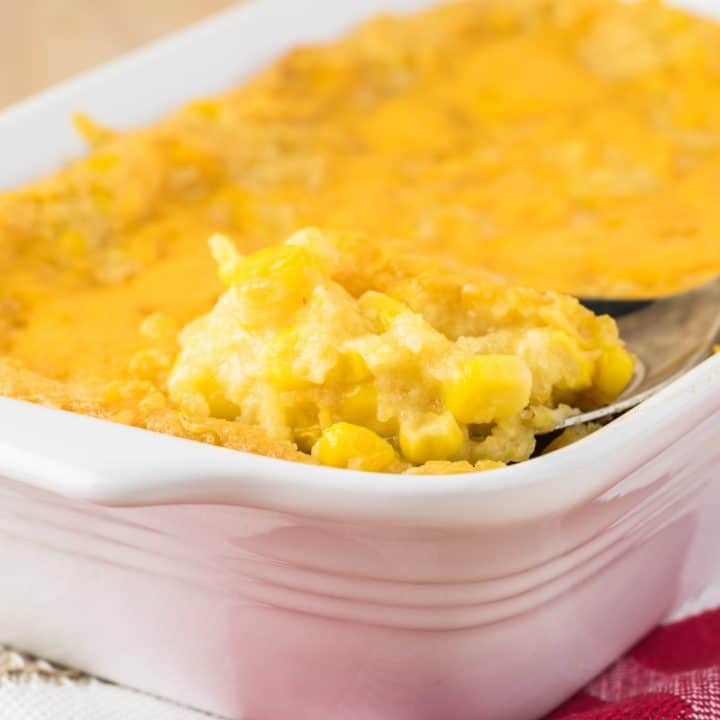 white baking dish with baked corn casserole sitting on kitchen towel