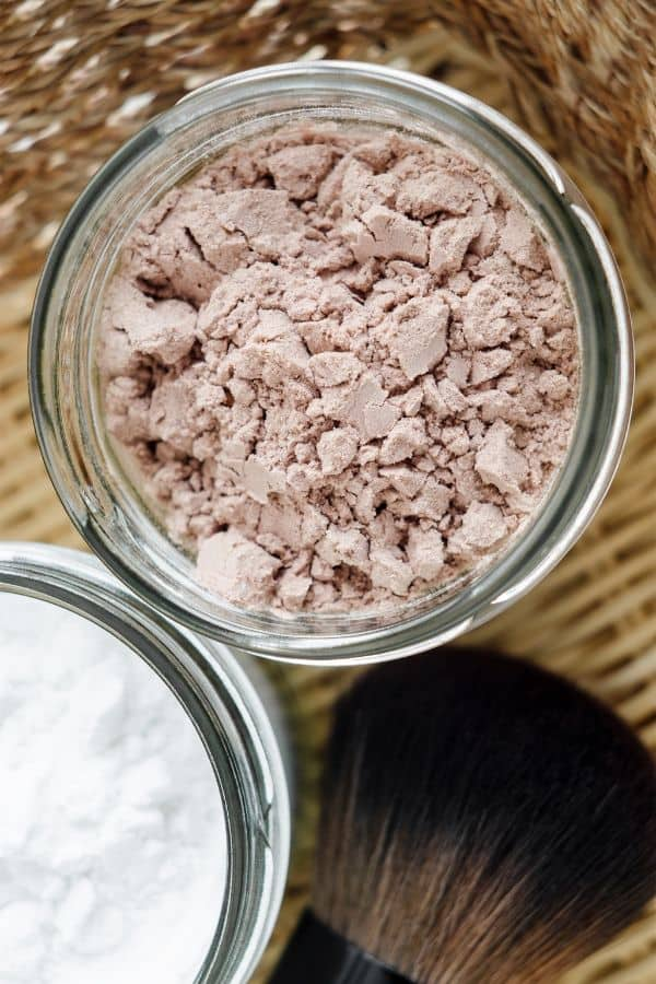 overhead view of dry shampoo in a glass jar with makeup brush