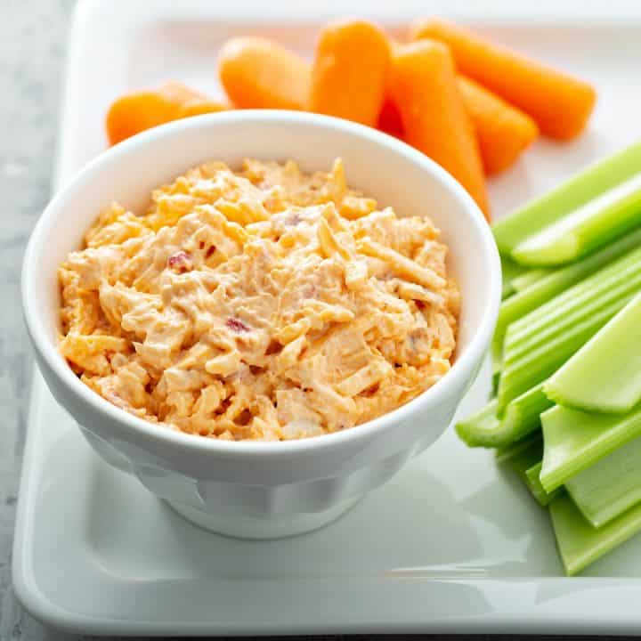 white bowl filled with southern pimento cheese spread on platter with carrots and celery