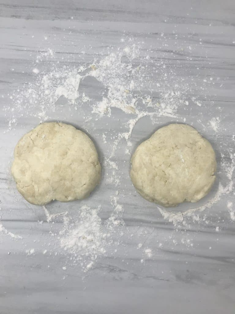 two pieces of cream cheese dough on marble counter