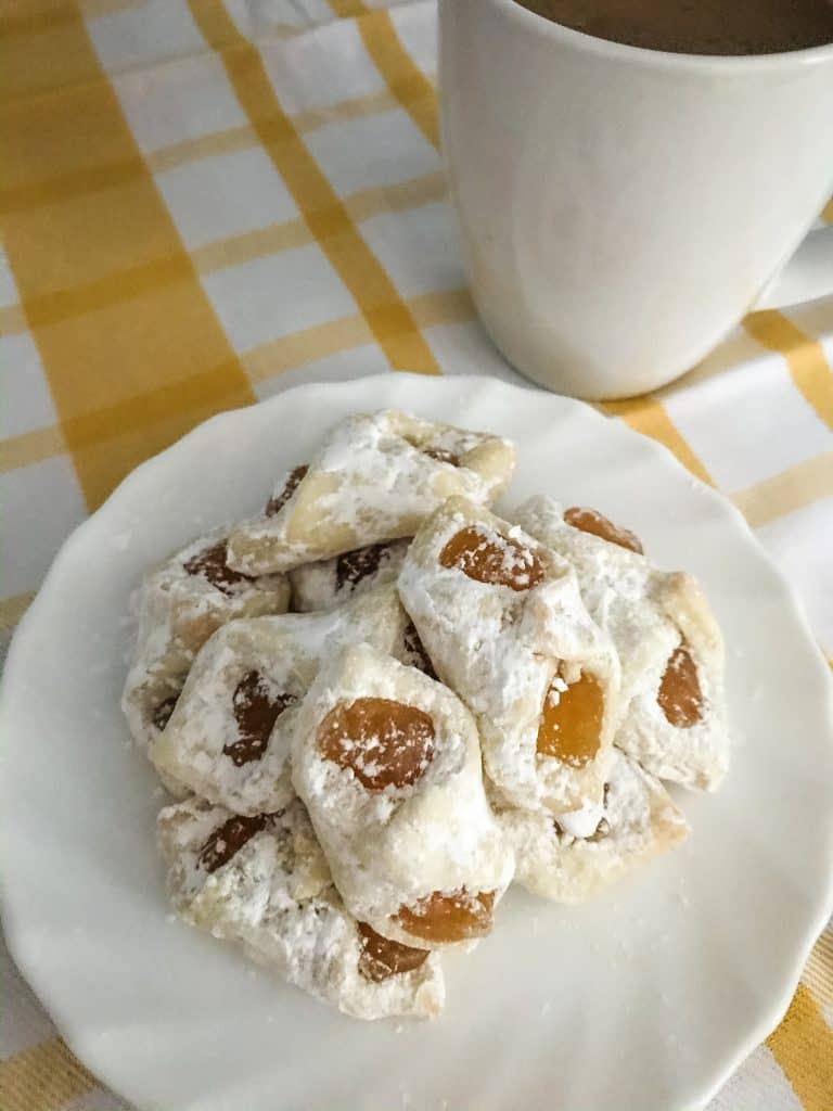 apricot kolaczki cookies on white plate with mug of coffee on yellow and white towel
