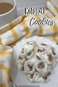 Apricot Kolaczki cookies on white plate with yellow and white towel and cup of coffee on marble counter