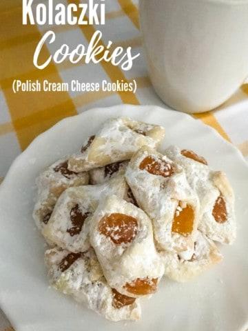 apricot kolaczki cookies on white plate on yellow and white towel