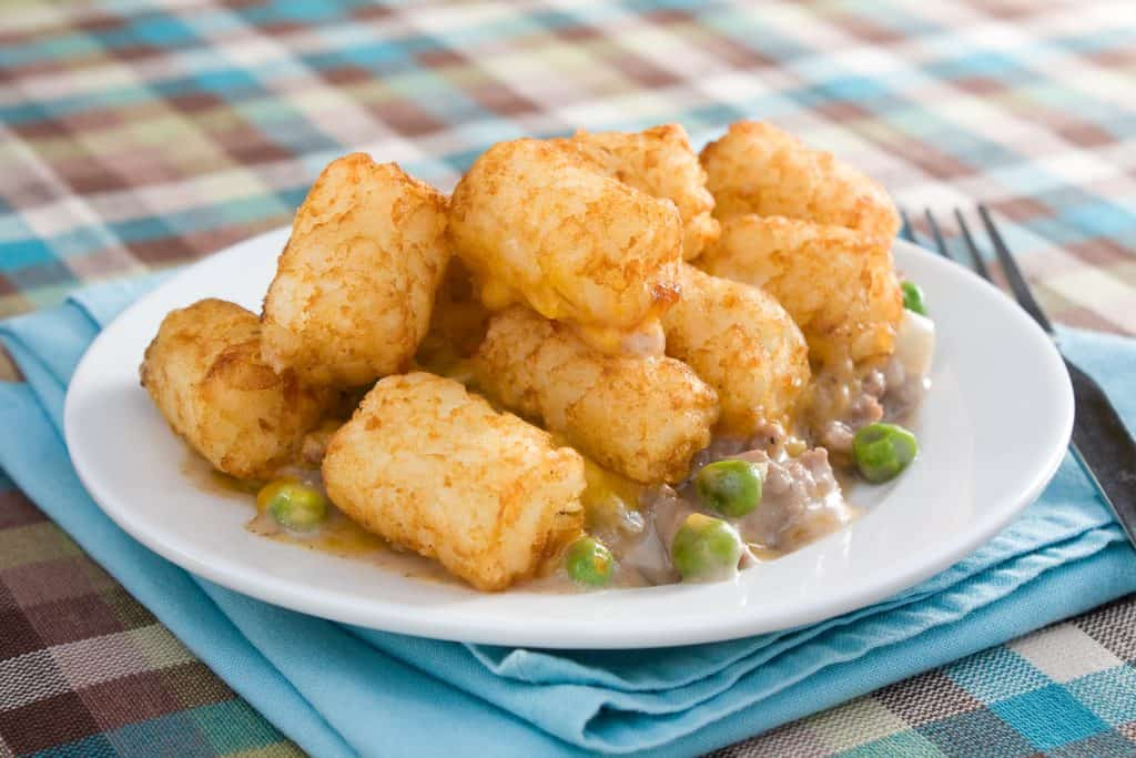 white plate with ground beef, peas and tater tots