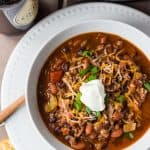 overhead of white bowl of chili on white plate with bottle of guinness beer and slow cooker