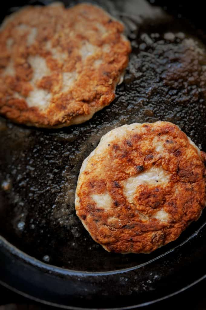 chicken salisbury steak patties cooking in cast iron skillet