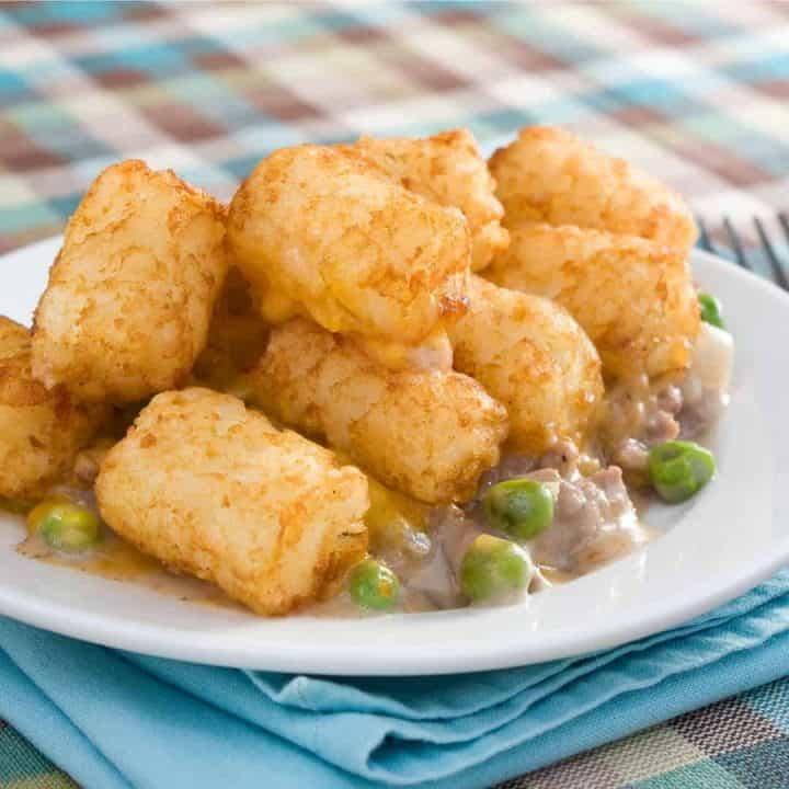 tater tots, ground beef, cream of mushroom soup and peas on white plate with blue napkin