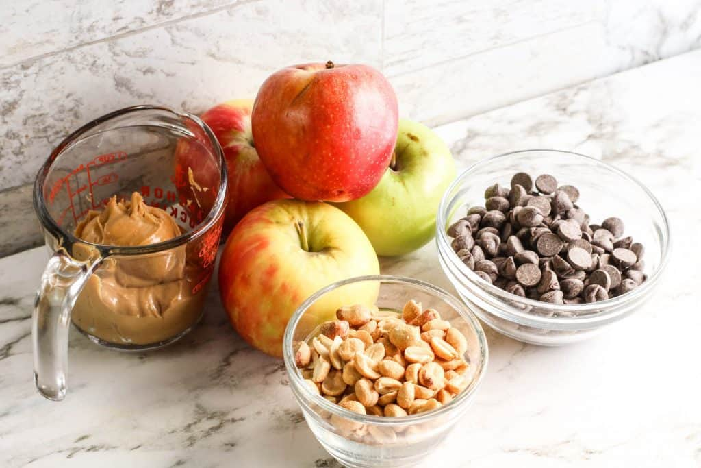 ingredients for apple nachos in glass bowls on marble counter