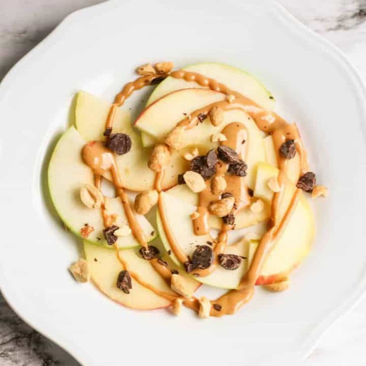 sliced apples on white plate topped with nut butter and chopped nuts and chocolate for apple nachos