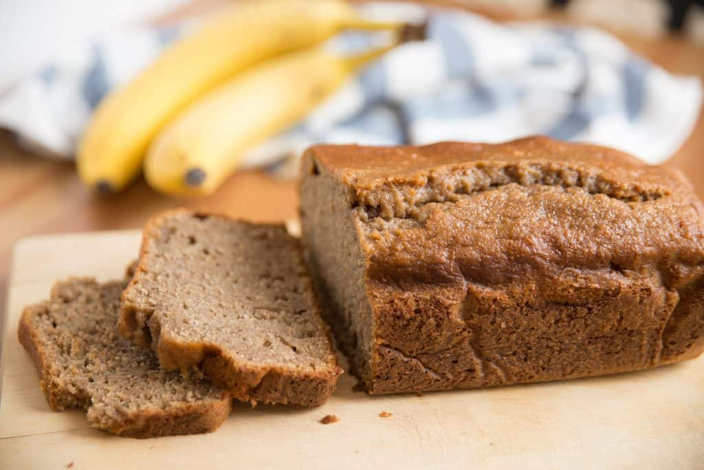 loaf of applesauce banana bread on wooden cutting board