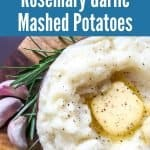 """bowl of instant pot mashed potatoes with garlic cloves and rosemary sprig on wooden cutting board with title text """"Instant Pot Rosemary Garlic Mashed Potatoes)"""