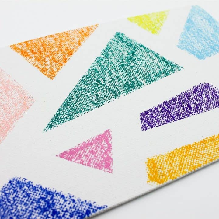 square image of white canvas board with oil pastel design