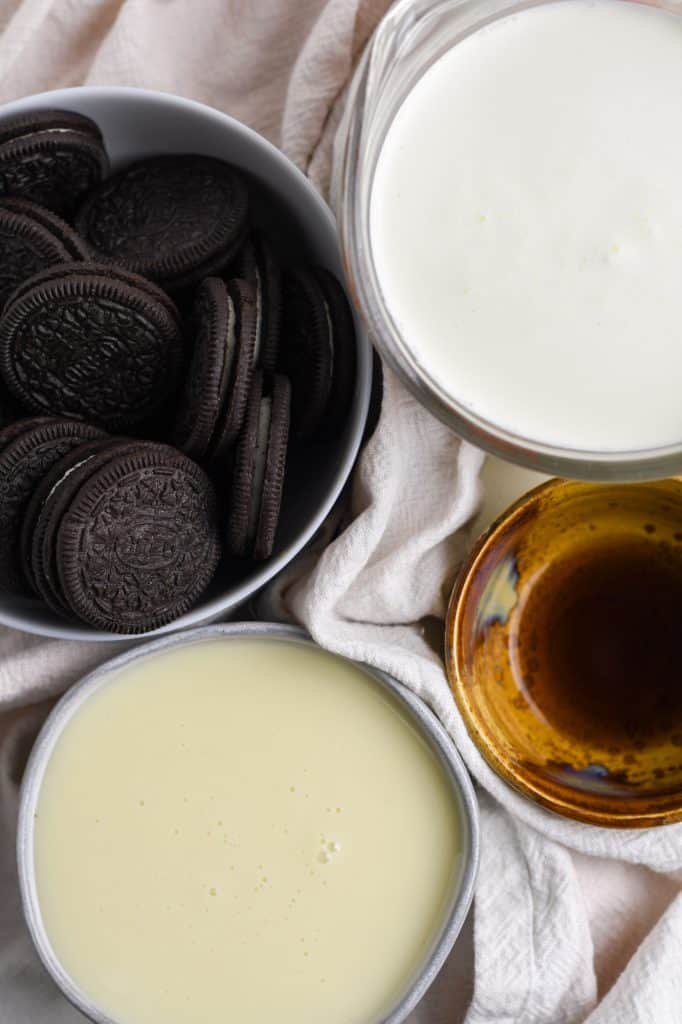 ingredients for no churn cookies and cream ice cream: oreo cookies, heavy whipping cream, vanilla, and sweetened condensed milk