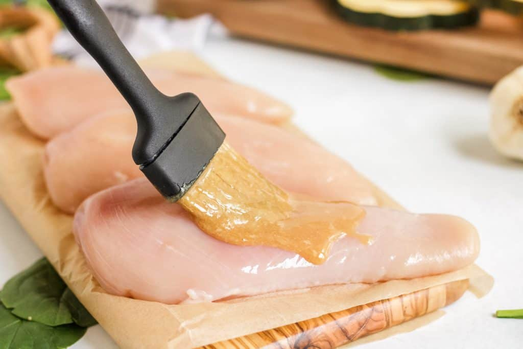 chicken breast on wooden cutting board brushed with maple mustard glaze