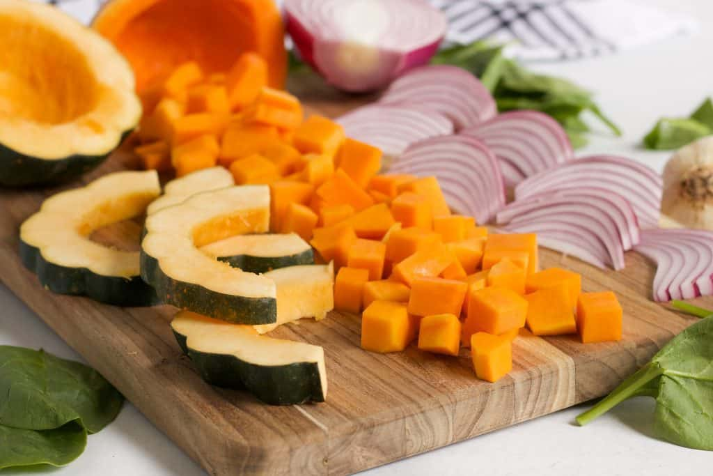 acorn squash, butternut squash and red onions cut on wooden cutting board