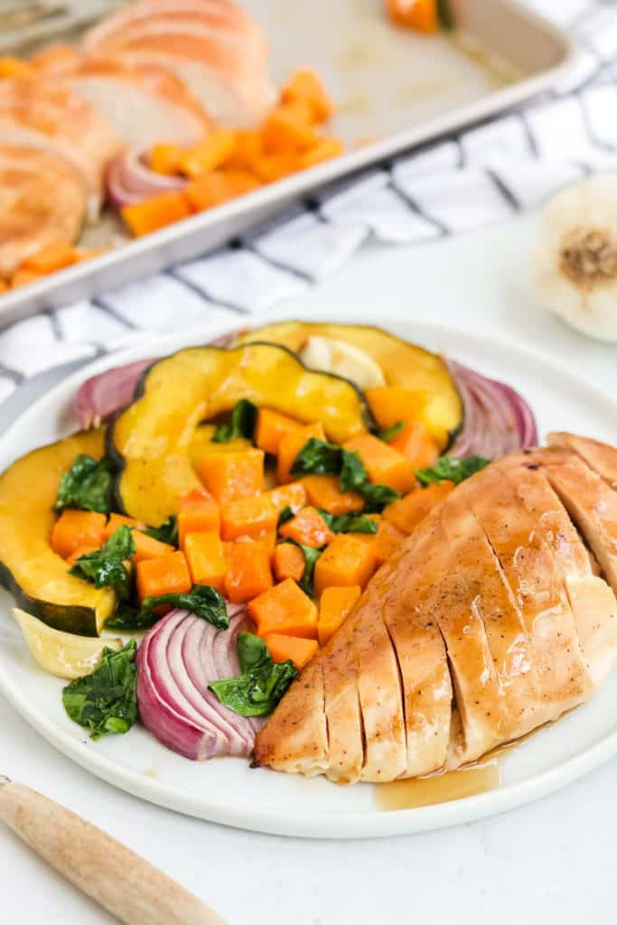 sliced chicken breast and roasted vegetables on white plate