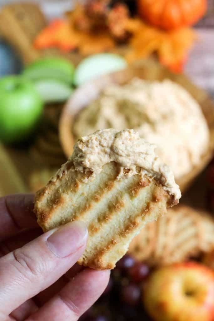 hand holding shortbread cookie dipped in pumpkin fluff dip