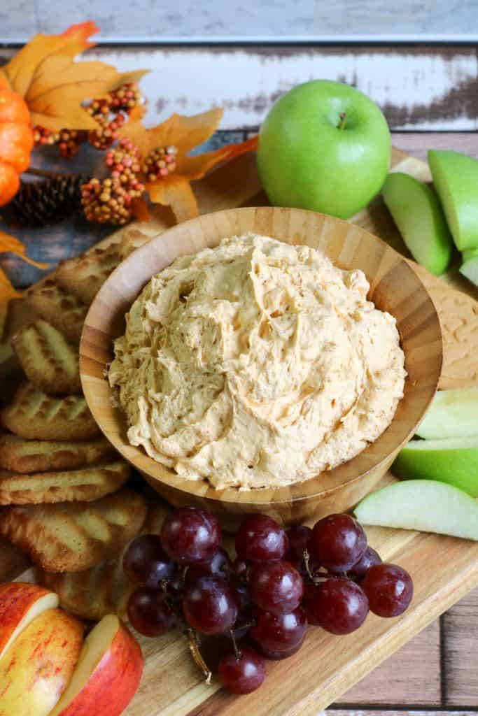 pumpkin fluff dip in wooden bowl with grapes, apple slices and shortbread cookies