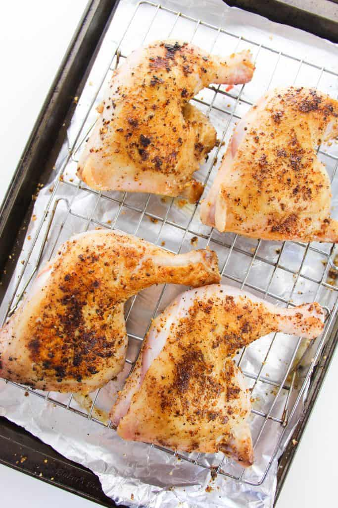 baked chicken leg quarters on baking sheet