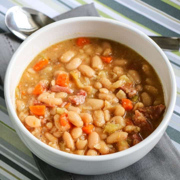 crock pot ham and bean soup in white bowl on striped tablecloth