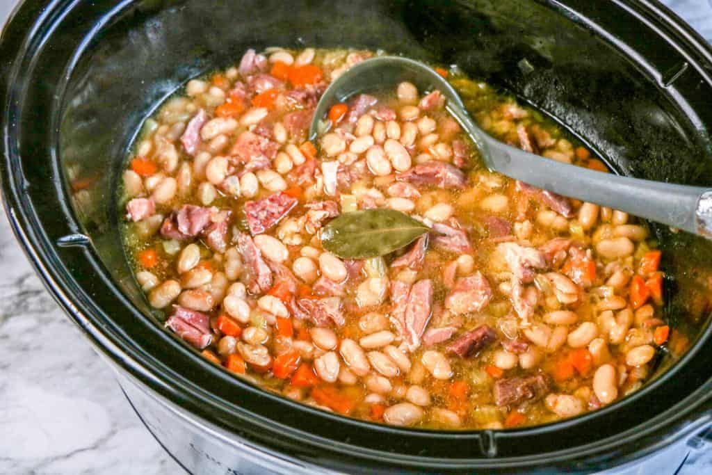 ham and bean soup in crock pot with ladle