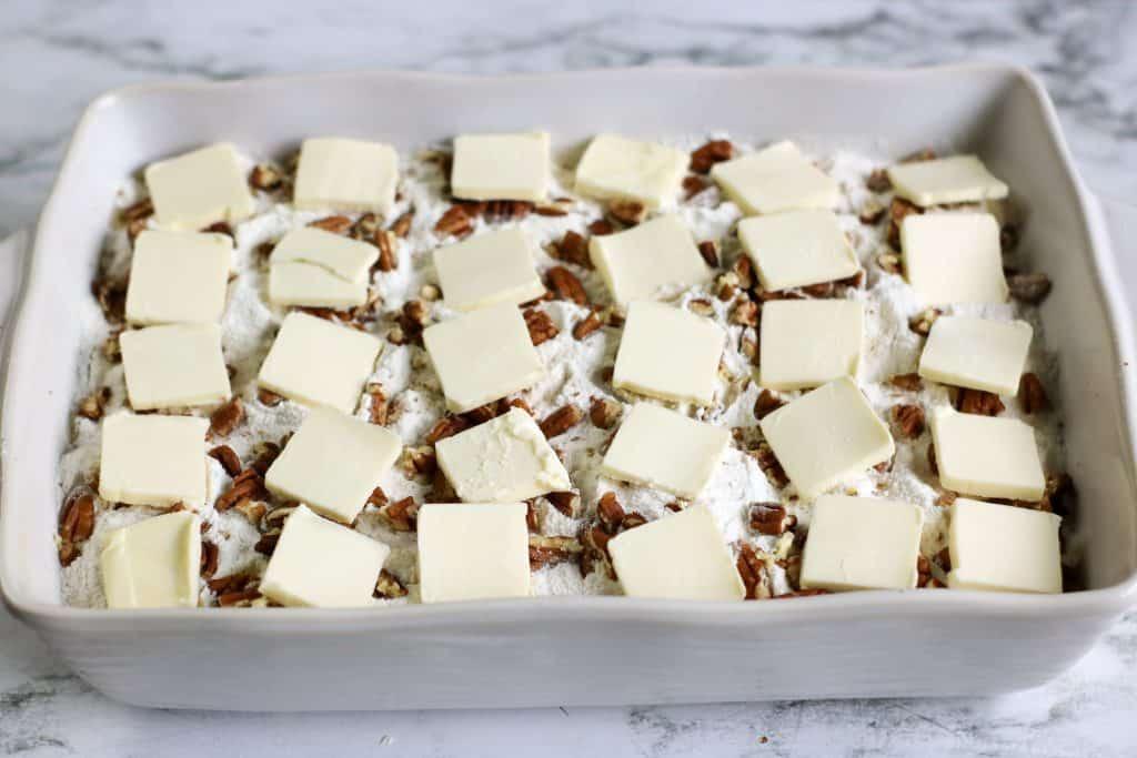 white baking dish with white chocolate peach dump cake ingredients layered