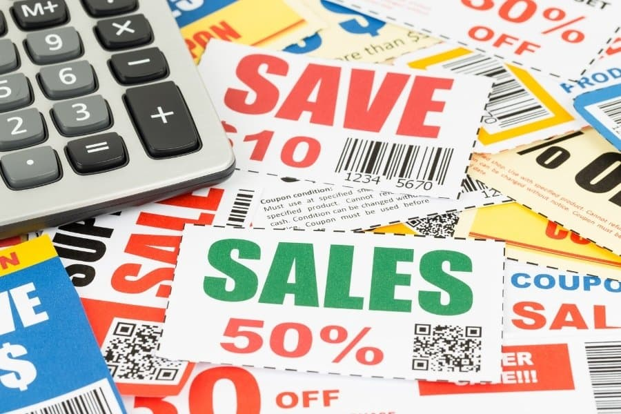 stack of coupons and calculator for extreme budgeting