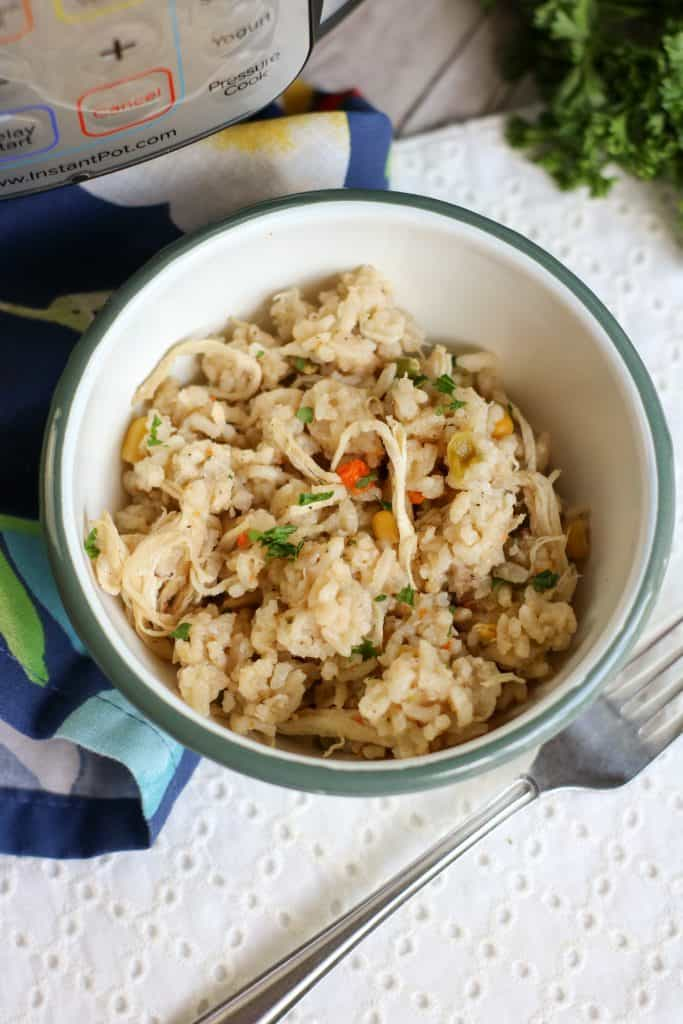 instant pot chicken and rice in white bowl with instant pot in background
