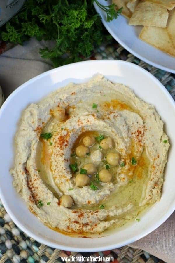 overhead of instant pot hummus in white bowl with chopped parsley and pita chips