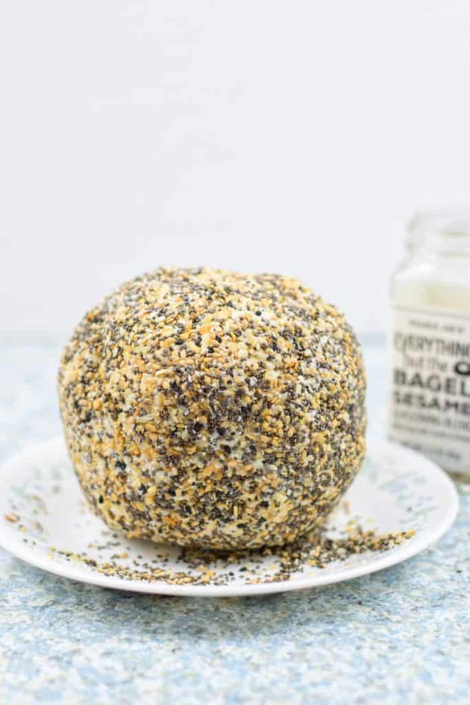 cheese ball coated in everything bagel seasoning on white plate