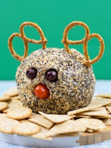 cheese ball coated in everything bagel seasoning with pretzels, black olives and tomato to look like reindeer