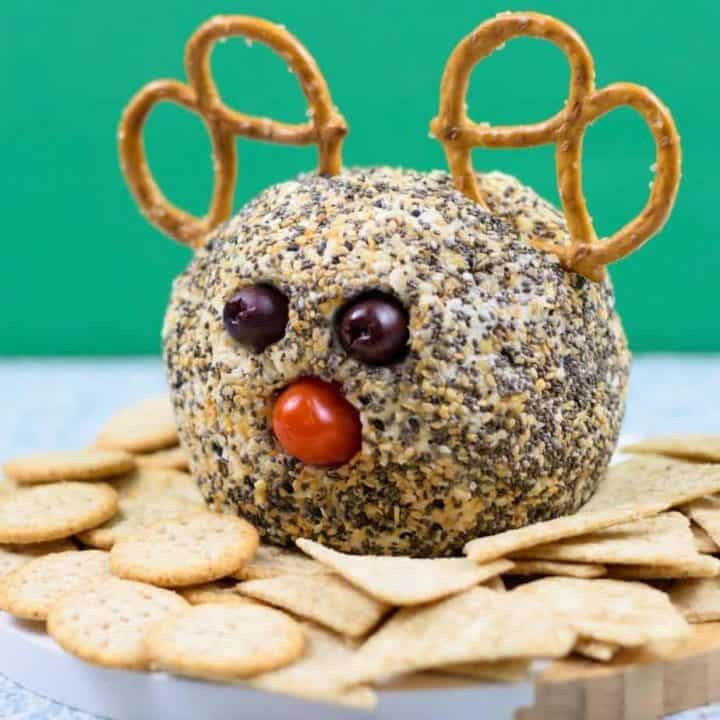 everything bagel cheese ball decorated like a reindeer on bamboo platter with crackers