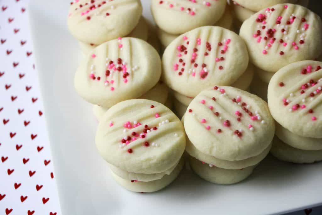 whipped shortbread cookies topped with pink nonpareils on square white plate