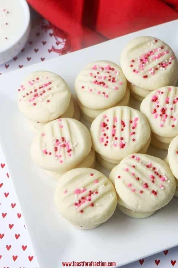 whipped shortbread cookies on square white plate with red napkin