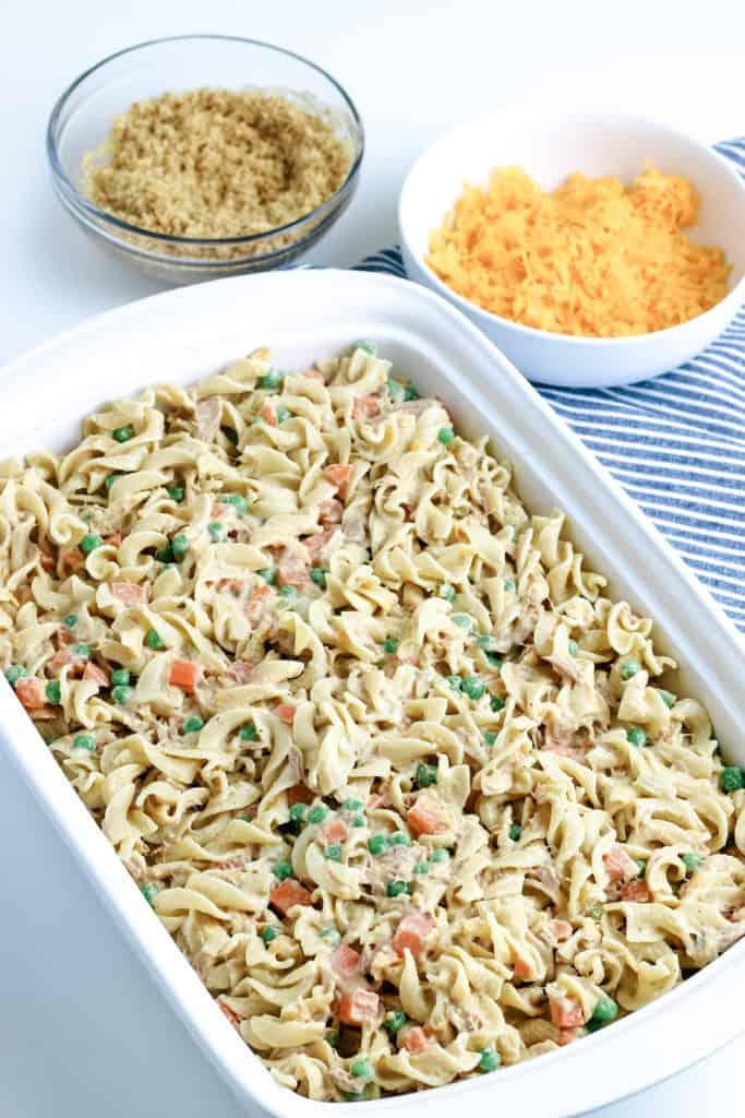 unbaked tuna noodle casserole in baking dish with breadcrumbs and shredded cheese