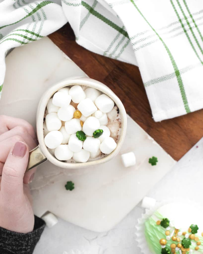 overhead view of peppermint hot cocoa in mug with marshmallows and shamrock sprinkles