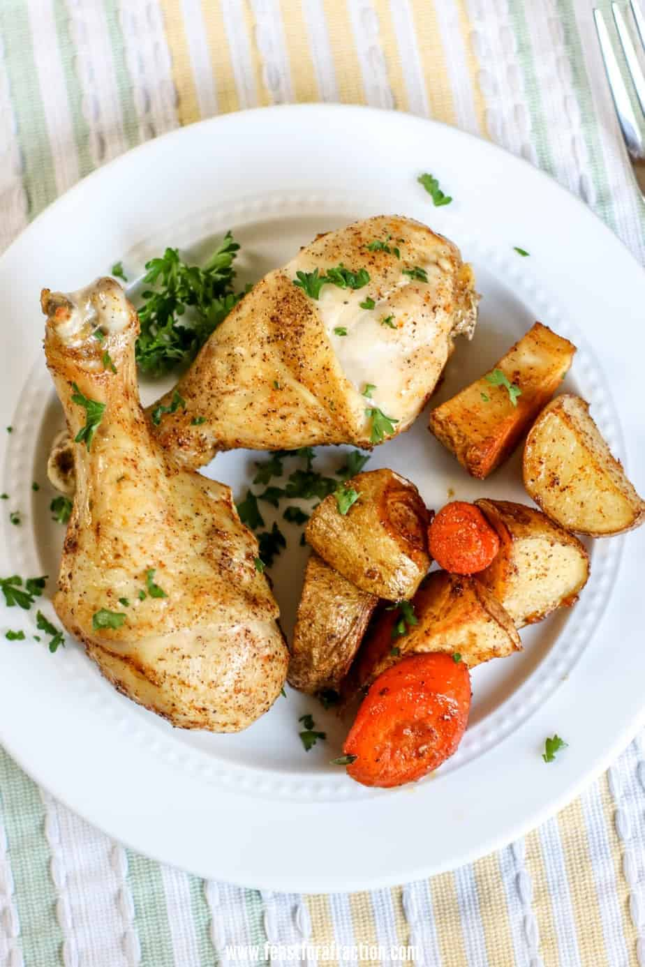 two chicken drumsticks and roasted carrots and potatoes on white plate with pastel tableclock