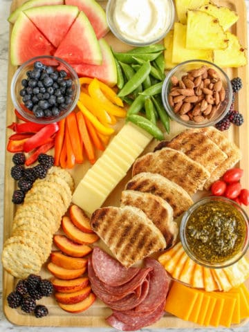 overhead view of charcuterie board with summer fruits and vegetables, bread and cheese