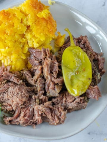 cooked crockpot mississippi pot roast on white plate with corn casserole and pepperoncini pepper